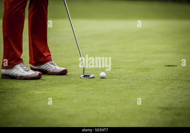 Golf player at hole - Stock Image
