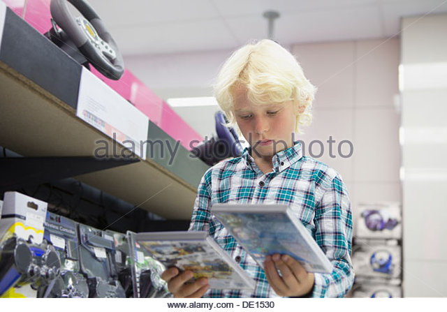 Boy looking at video games in electronics store - Stock Image