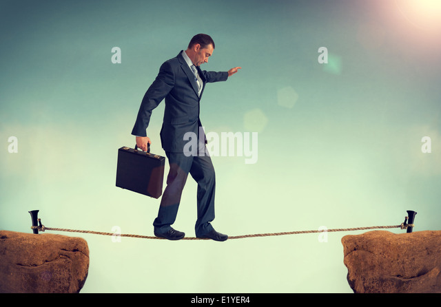businessman predicament balancing or walking a tightrope or highwire. business concept of challenge, risk, danger, - Stock Image