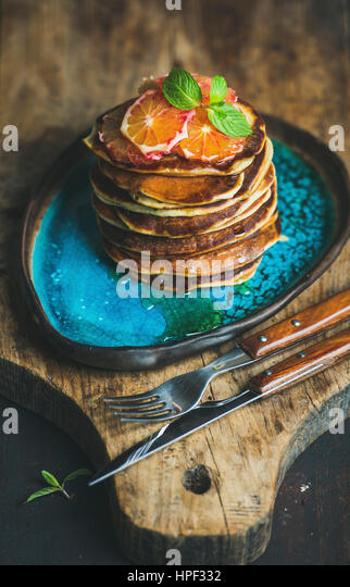 Homemade pancakes with honey, bloody orange slices and mint leaves for breakfast on blue ceramic plate over rustic - Stock Image