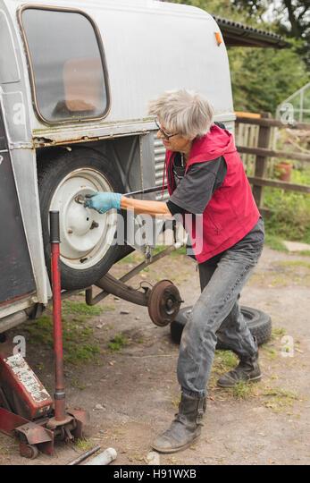 Elderly car mechanic replacing spare wheel - Stock-Bilder
