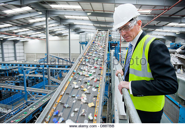 Businessman watching plastic on conveyor belt in recycling plant - Stock-Bilder