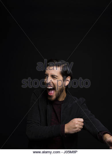 Portrait exuberant brunette man with beard laughing and looking away against black background - Stock Image