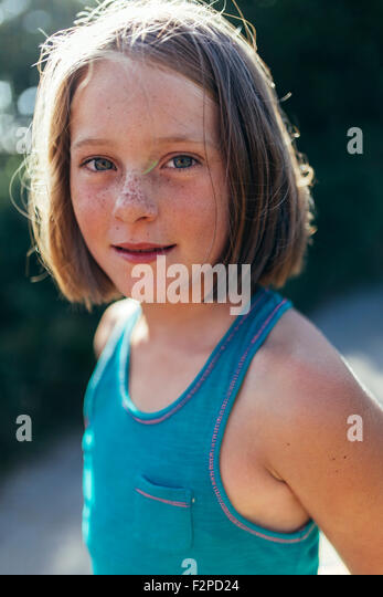 Portrait of smiling girl with brown hair and freckles - Stock Image