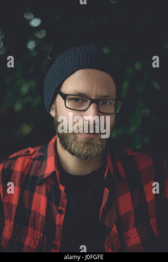 Authentic portrait of a handsome hipster man sitting on his porch. - Stock Image