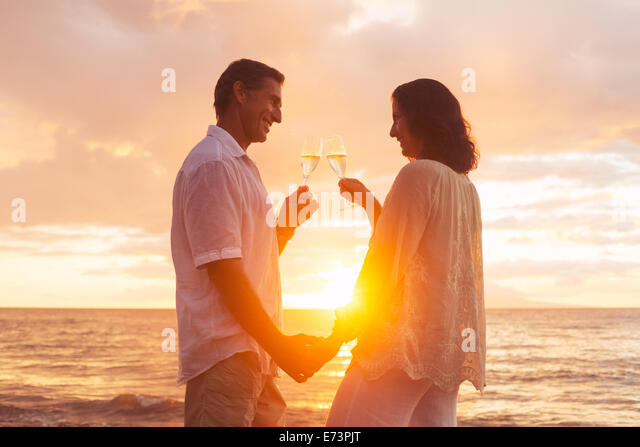 Happy Romantic Couple Enjoying Glass of Champagne at Sunset on the Beach. Vacation Travel Retirement Anniversary - Stock-Bilder