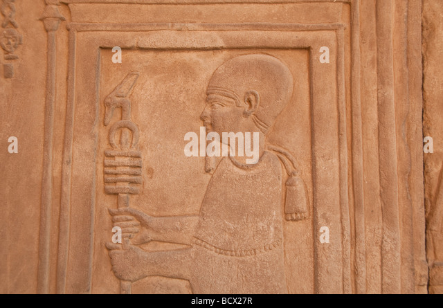 Egypt Kom Ombo temple wall carving relief hieroglyph man figure holds staff - Stock Image