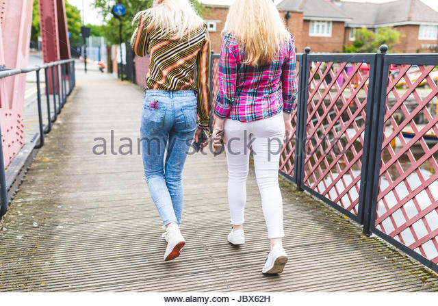 Two female friends walking across bridge, holding smartphones, rear view - Stock-Bilder