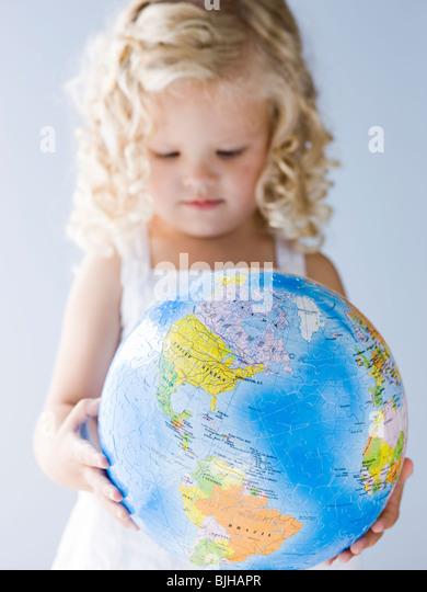 little girl holding a globe - Stock Image