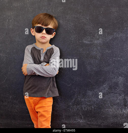 Portrait of smart little boy wearing sunglasses standing with his hands folded against blackboard with copyspace. - Stock Image