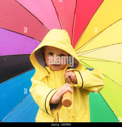 Boy in a raincoat holding a multi-colored umbrella - Stock Image