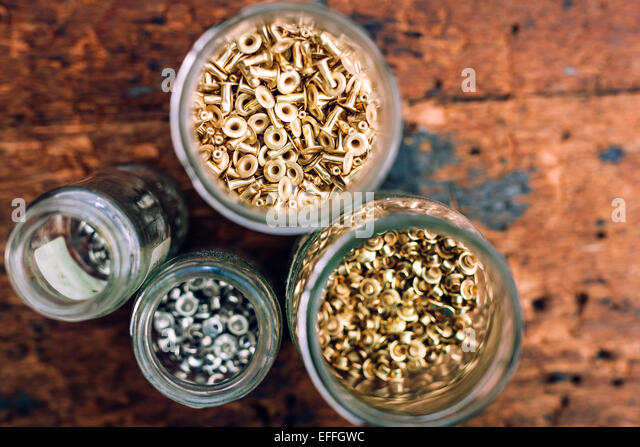 Directly above shot of jars filled with nuts on table at workshop - Stock Image