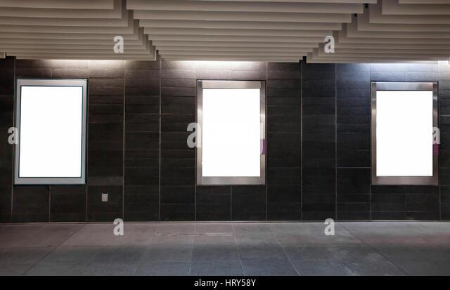 three empty white blank banners billboards in the dark modern urban corridor - Stock Image
