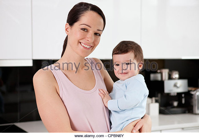 A young mother standing in a kitchen holding her baby son - Stock-Bilder