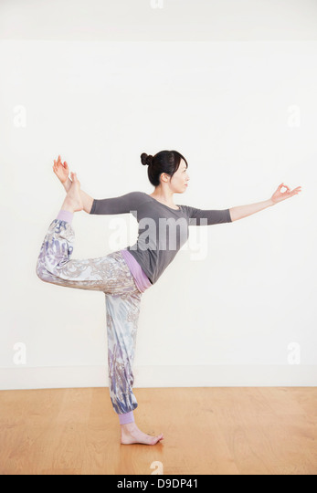 Woman standing on one leg, side view - Stock Image