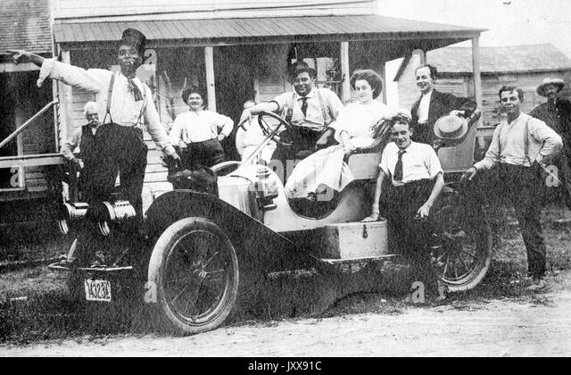 A group of people, including eight men and two women, mostly smiling, stand on or around a car, with one African - Stock Image