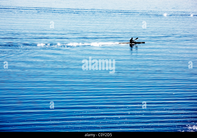 silhouette of a canoe rower practicing on lake - Stock Image