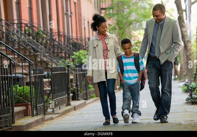 A family outdoors in the city. Two parents and a young boy walking together. - Stock-Bilder