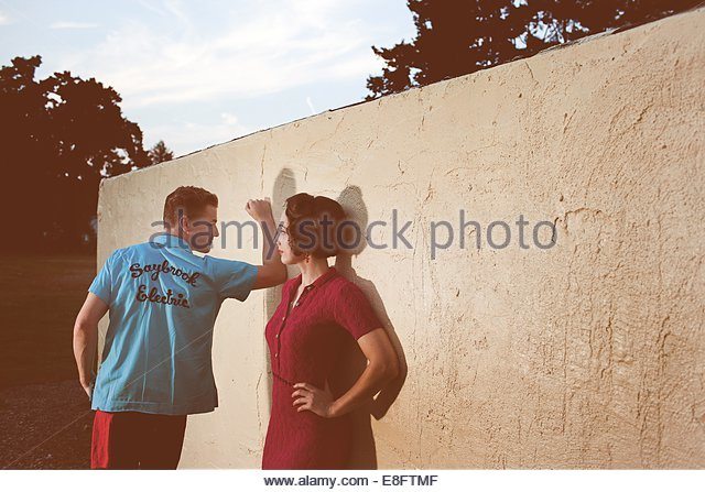 Young couple outdoors by wall - Stock Image
