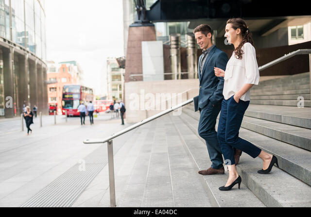 Rear view of young businessman and woman chatting whilst walking down stairway, London, UK - Stock Image