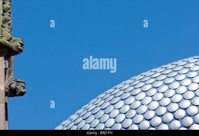 Contrasting image of the ultra modern Selfridges building in Birmingham, UK, with the old gargoyles on St Martin's - Stock Image
