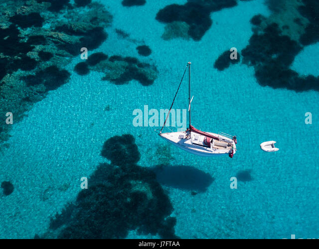 Aerial view of a boat in front of the Mortorio island in Sardinia. Amazing beach with a turquoise and transparent - Stock Image