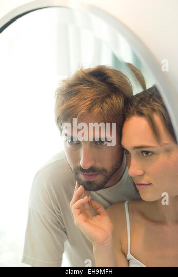 Couple looking into mirror together, wife caressing husand's bearded chin - Stock-Bilder