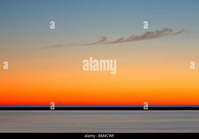 A single, feather-like cloud drifts across a brilliant twilight sky in Ludington, Manistee County, Michigan - Stock Image