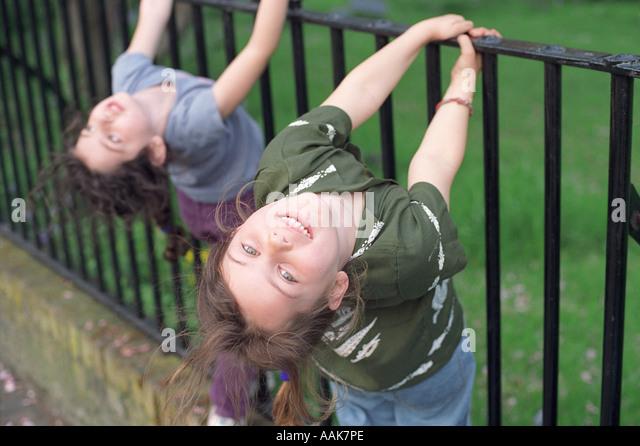 Two six year old girls playing on metal railings, London, UK. - Stock Image