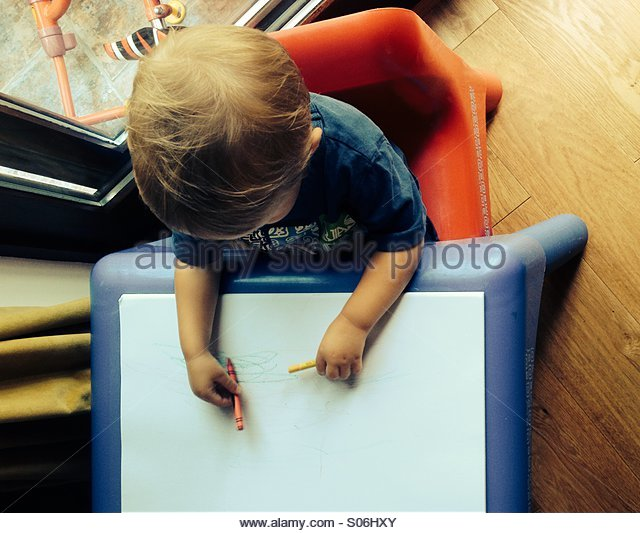 Toddler drawing first scribbles on paper with crayons - Stock-Bilder