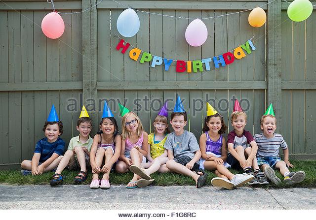 Portrait smiling kids a row backyard birthday party - Stock Image