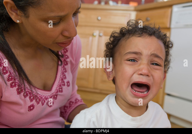 Worried Hispanic mother beside her crying son - Stock Image