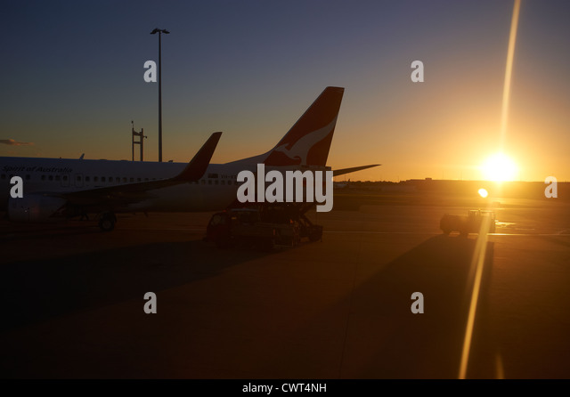 Qantas jets in silhouette on the tarmac at the Brisbane airport terminal Australia - Stock Image