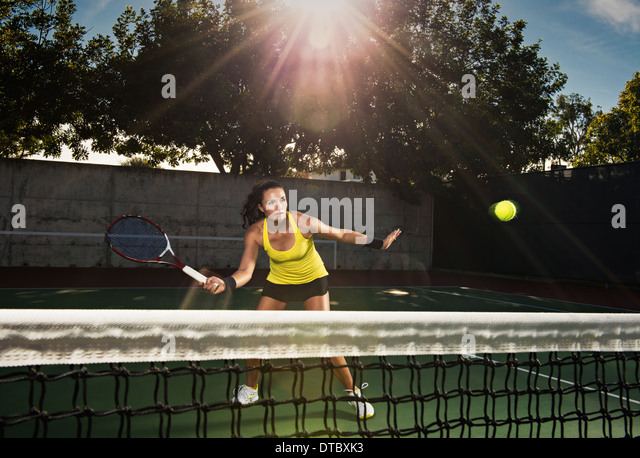 Female tennis player hitting ball over net - Stock Image