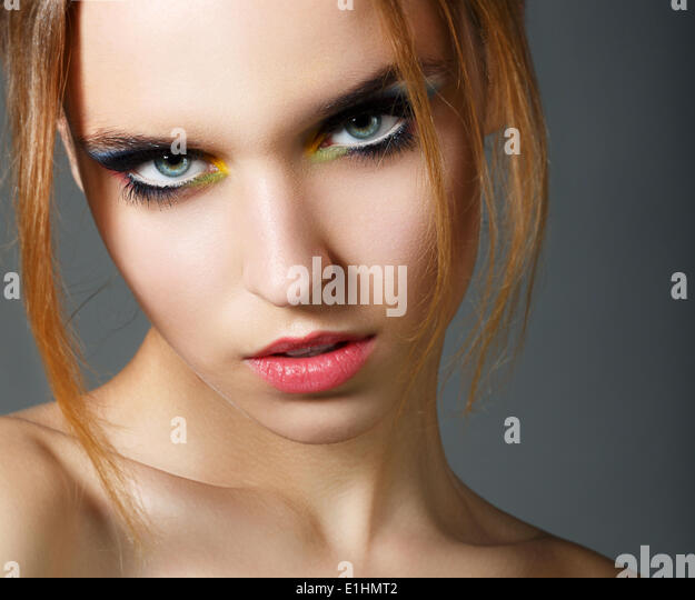 Magnetism. Character. Face of Young Red Hair Beauty with Colorful Eye Makeup - Stock Image