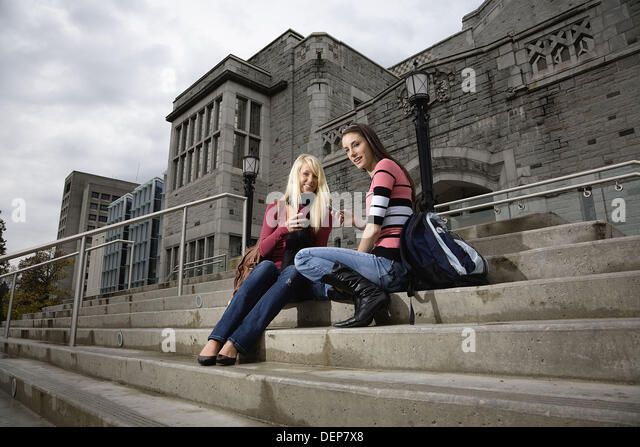 Portrait of two female college students sitting on the steps of a building, University of British Columbia, Vancouver, - Stock Image
