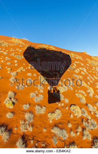 Brilliant reddish-orange sand dunes dotted with hardy grasses in a desert landscape viewed from a hot air balloon. - Stock-Bilder