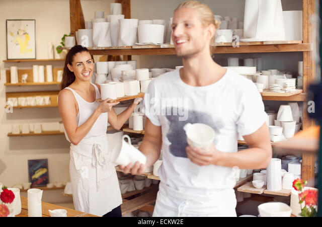 Happy workers arranging craft products at crockery workshop - Stock Image