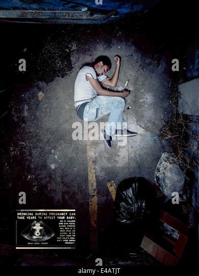 SANCA 2010 fetal alcohol syndrome awareness campaign poster. Drug addict in fetal position. See description for - Stock Image