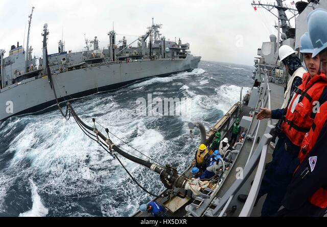 Military Sealift Command fast combat support ship USNS Rainier (T-AOE-7) and Arleigh Burke-class guided-missile - Stock Image
