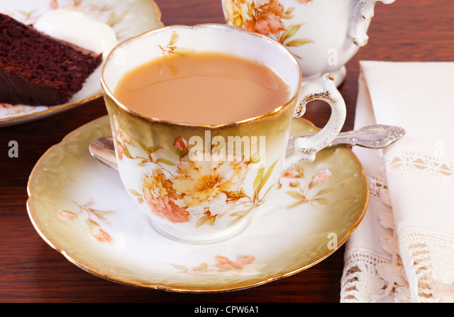 Afternoon tea set out on a dark oak table, with a cup of tea and chocolate cake, delicious nostalgia! - Stock Image