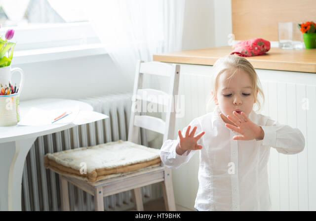 Little girl trying to dry her freshly painted finger nails - Stock Image