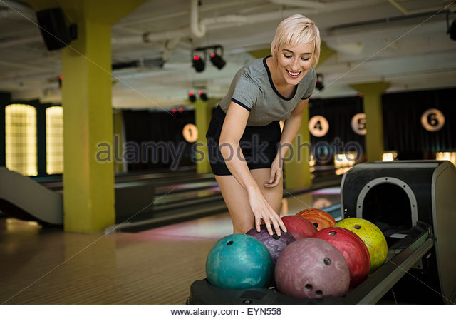 Young woman choosing bowling ball from rack - Stock Image