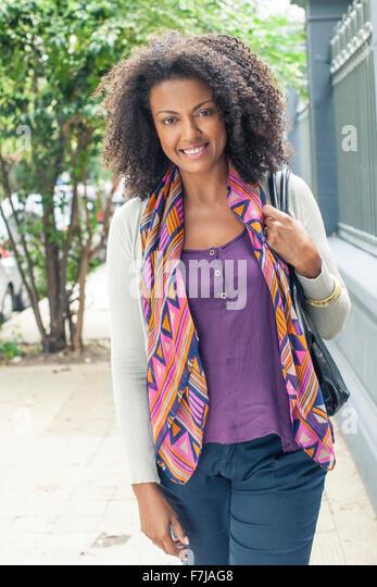 Woman standing on sidewalk, portrait - Stock Image