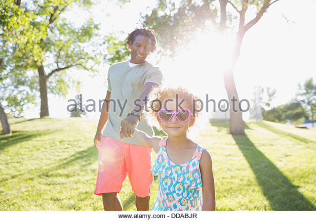 Daughter and father holding hands on a walk - Stock Image