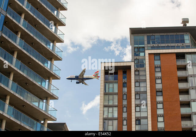A plane flying past apartment blocks as it comes into land at City Airport, London, UK. - Stock Image