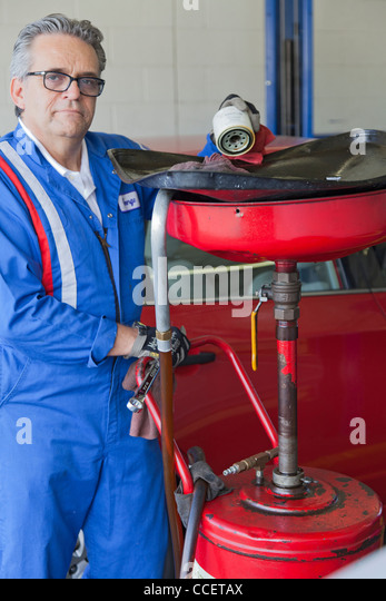 Portrait of senior mechanic standing besides car spray paint equipment - Stock Image