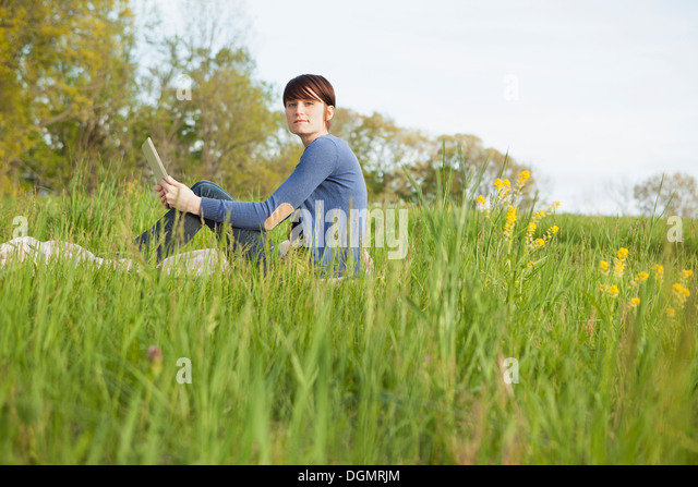 A young woman sitting in an open space, a grass field, on a blanket, holding a digital tablet. - Stock Image