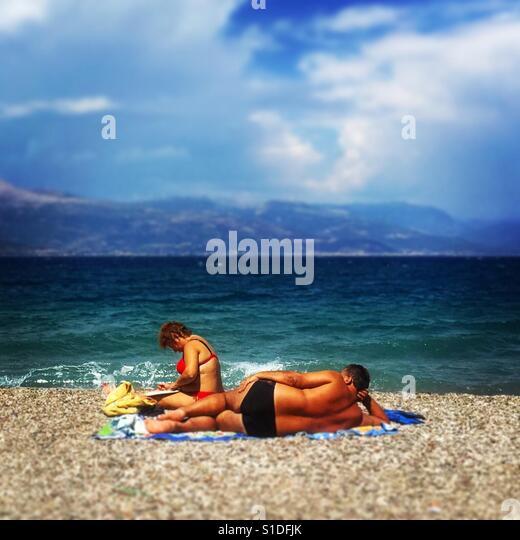 A couple sunbathe in Greece. - Stock-Bilder