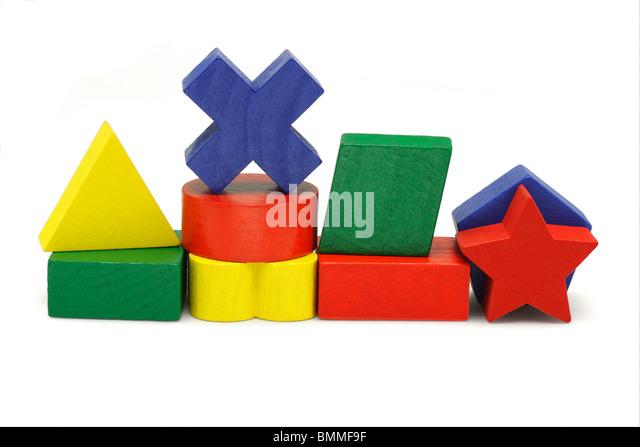 Wooden geometric toy blocks on white background - Stock Image